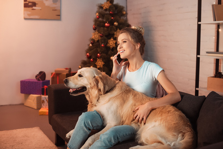 Beautiful Young Blonde Woman Sitting On Couch With Golden Retriever