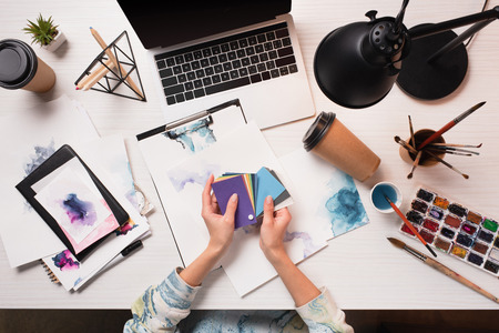 cropped designer working at office desk with laptop and art supplies 스톡 콘텐츠