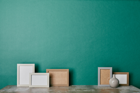 Different photo frames and vase on green background
