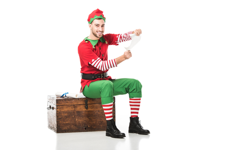cheerful man in christmas elf costume sitting on wooden chest and holding wishlist isolated on white Stock Photo