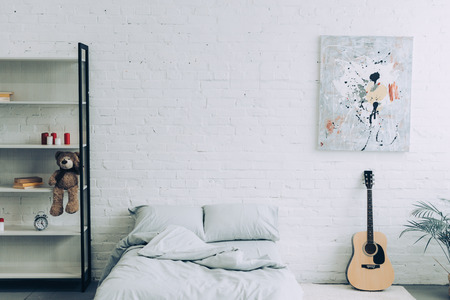 high angle view of modern bedroom with shelves, guitar and painting on white brick wall