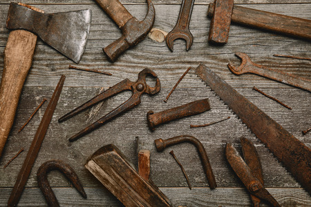 Top view of various rusty carpentry tools on wooden background