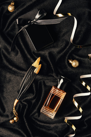 top view of perfumes, decorative feathers, golden ribbons and christmas baubles on black fabric