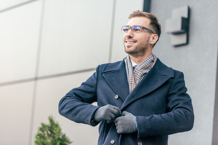 adult smiling handsome man in glasses fastening coat near building 免版税图像