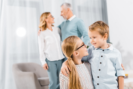 adorable kids looking at each other and embracing while their grandparents standing behind at home