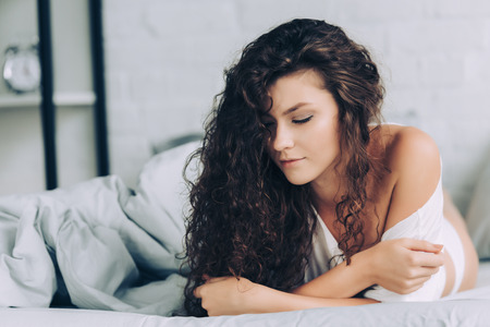 selective focus of curly young woman laying in bed during morning time at home