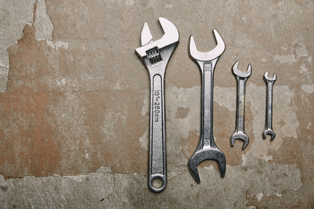 Top view of set of wrenches tools and one monkey wrench on the background of old  surface