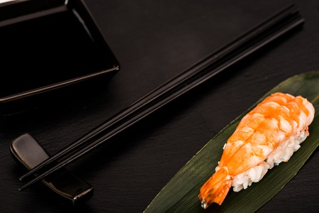 Close up of nigiri sushi with shrimp served with chopsticks and soy sauce on black slate Stock Photo