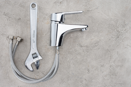 top view of water mixer and pipe wrench on concrete surface 写真素材