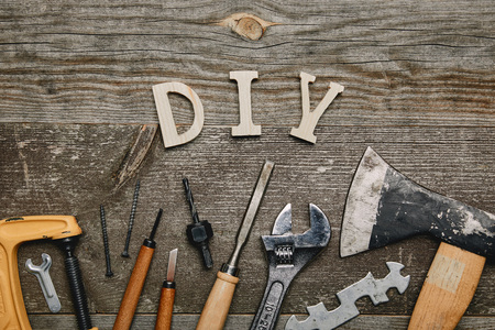 Flay lay with different carpentry tools and diy sign on wooden background Stock Photo - 112385700