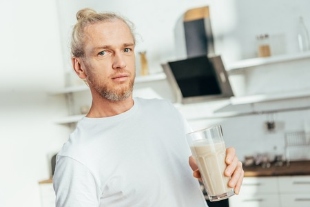 athletic man holding glass with protein shake and looking at camera