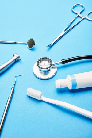close up view of arrangement of sterile dental instruments, stethoscope, toothbrush and toothpaste on blue backdrop, dental care concept Banco de Imagens