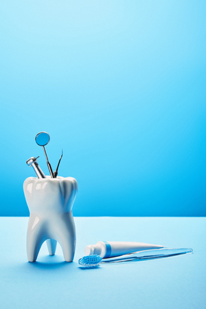 close up view of white tooth model, toothbrush, toothpaste and stainless dental instruments on blue backdrop 免版税图像 - 112385743