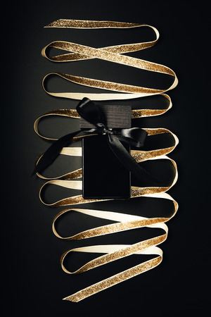 black perfume bottle with bow and shiny golden ribbon on black