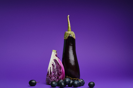 close-up view of sliced cabbage, grapes and eggplant on purple