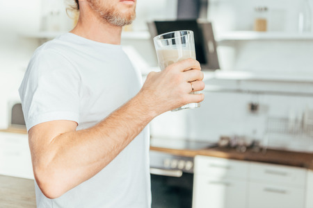 cropped shot of man holding glass with protein shake at home