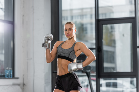 attractive muscular bodybuilder posing with silver boxing gloves in gym and looking at camera Stockfoto