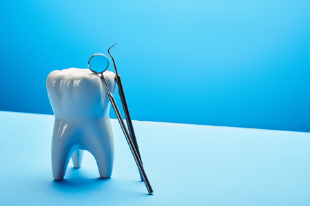 close up view of tooth model, dental mirror and probe on blue backdrop Banque d'images - 112385780