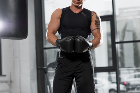 midsection of muscular boxer standing with boxing gloves in gym Stockfoto