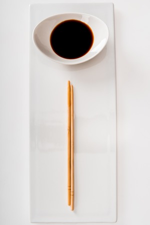 Top view of plate with soy sauce and chopsticks on white slate