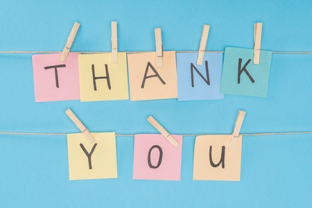 colorful sticky notes spelling thank you on lace with clothespins isolated on blue background Фото со стока