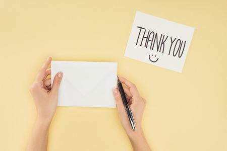 cropped person holding pen and blank sheet of paper, white postcard with thank you lettering isolated on yellow background