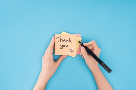 Persona recortada sujetando la pluma encima de coloridas notas adhesivas con letras de agradecimiento aislado sobre fondo azul. Foto de archivo