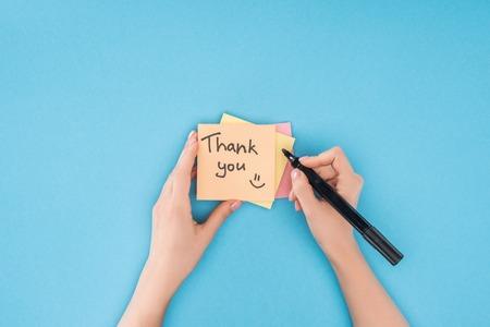 persona ritagliata tenendo la penna sopra foglietti adesivi colorati con scritte di ringraziamento isolate su sfondo blu blue Archivio Fotografico