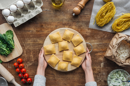 top view of female hands holding chopping board with ravioli at wooden table
