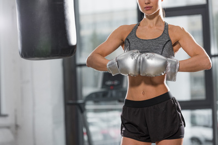 cropped image of athletic boxer standing with silver boxing gloves in gym Stockfoto