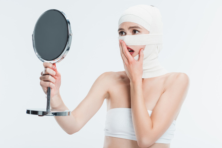 shocked woman with bandages over head looking at mirror isolated on white