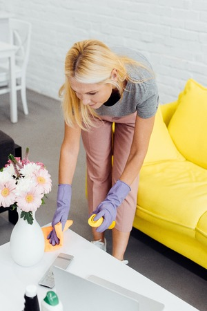 mature woman in gloves cleaning table from dust Фото со стока