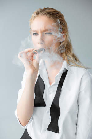 elegant stylish blonde girl smoking cigar isolated on grey