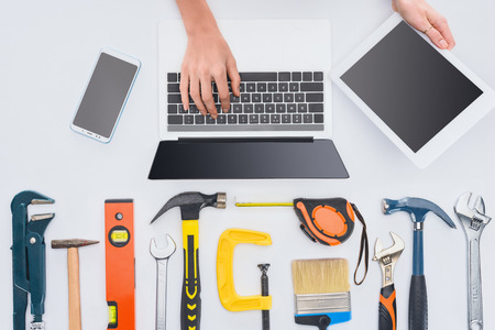 cropped shot of woman using gadgets with various tools lying on white Stock Photo