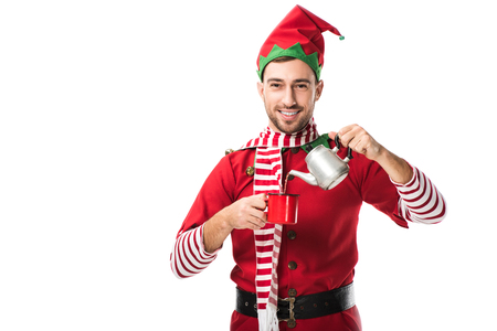 happy man in christmas elf costume with metal kettle pouring tea in cup and looking at camera isolated on white