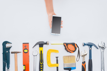 cropped shot of woman using smartphone with various tools lying on white Stock Photo