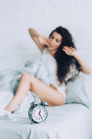 selective focus of alarm clock on bed and woman waking up during morning time in bedroom at home Stockfoto