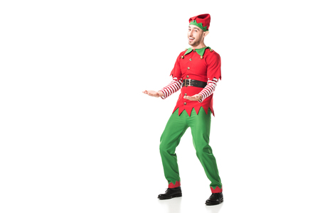 cheerful man in christmas elf costume outstreching hands in excitement isolated on white Foto de archivo - 112385999