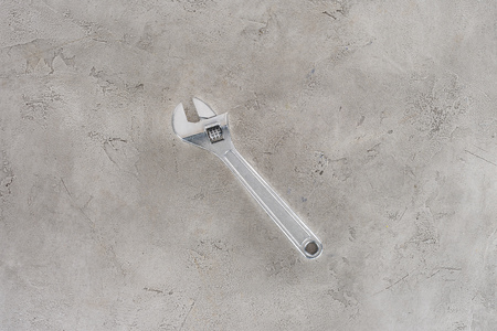 top view of pipe wrench lying on concrete surface