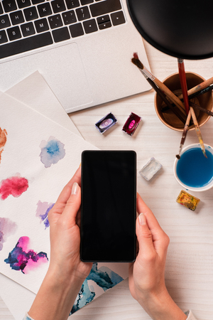 cropped view of designer at office desk holding smartphone with blank screen, flat lay