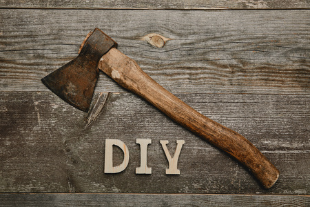 Top view of vintage rusty axe and duy sign on woodem background