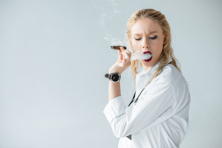 elegant blonde girl smoking cigar isolated on grey 스톡 콘텐츠