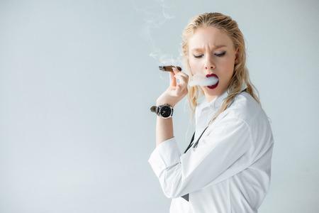 Elegantes blondes Mädchen, das Zigarre raucht, isoliert auf grau