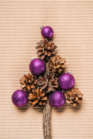 Flat lay of purple christmas balls and pine cones in the form of Christmas tree on the textured background