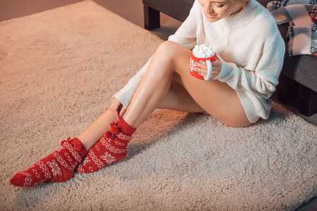 beautiful woman in christmas patterned socks drinking cocoa