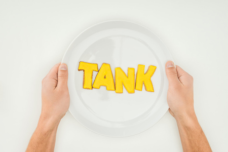 cropped person holding plate with tank word in yellow cookies isolated on white background