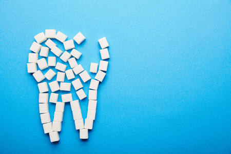 top view of white sugar cubes arranged in tooth sign on blue background, dental care concept 写真素材 - 112386255