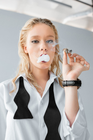 beautiful fashionable blonde girl smoking cigar on grey