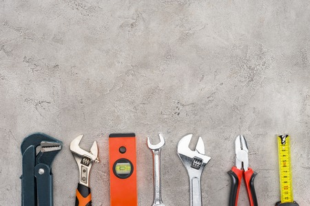flat lay with row of various tools on concrete surface 写真素材