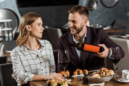Happy young adult couple having dinner while man pouring wine in glasses in restaurant